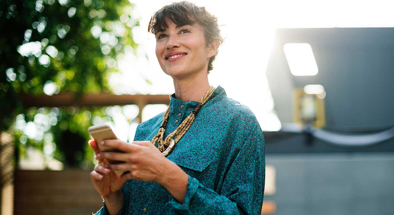 woman smiling with smartphone represents the consumer