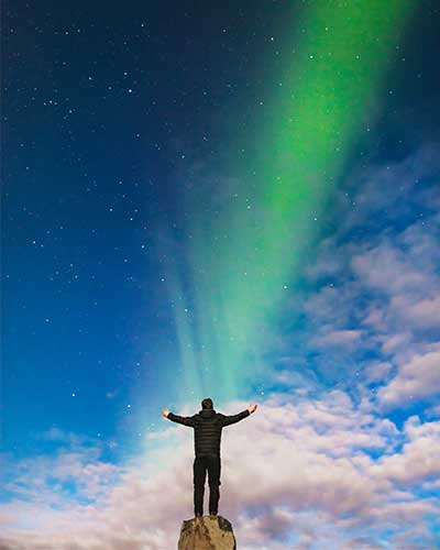 Man watching an aurora borealis represents a quality implementation methodologies