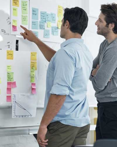Two people looking at a post-it white board represents the agility of processes and successful solutions