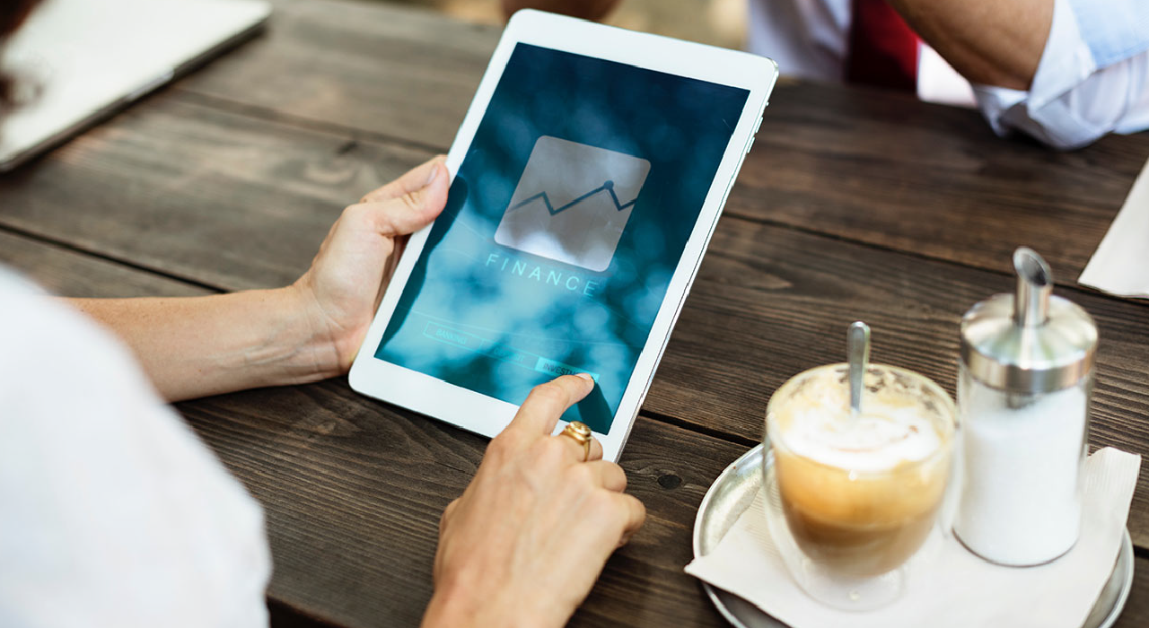 header, Person touching in a tablet at the coffee represents Insights NAV that makes key business indicators available in real-time along with numerous financial analysis options