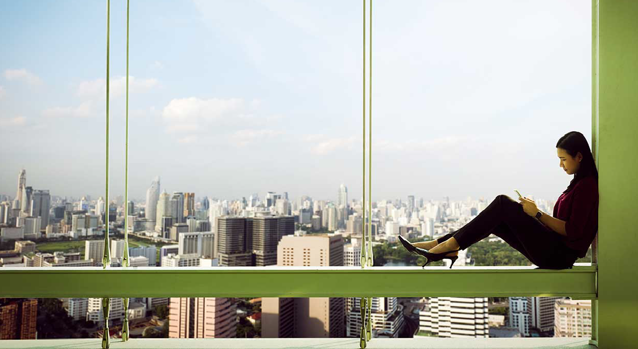 Woman seated near by a window with big city landscape