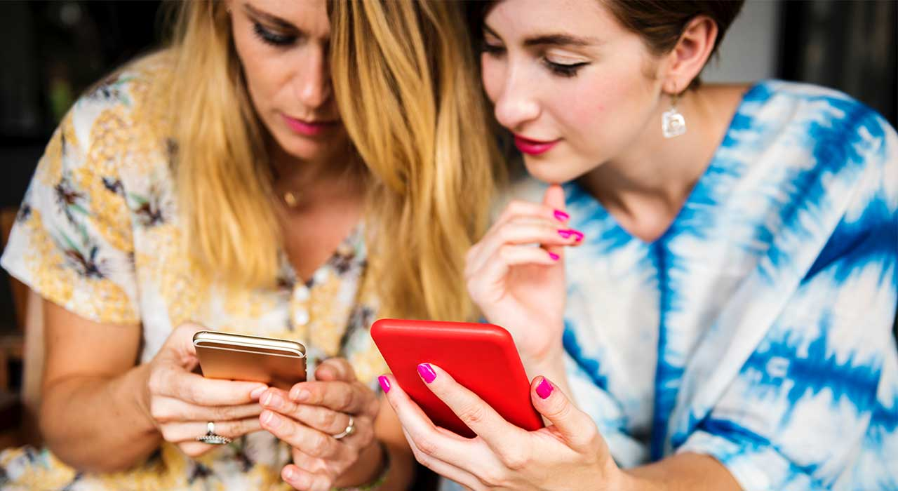 Two women looking at their mobile phones represents the improvement of the User Experience